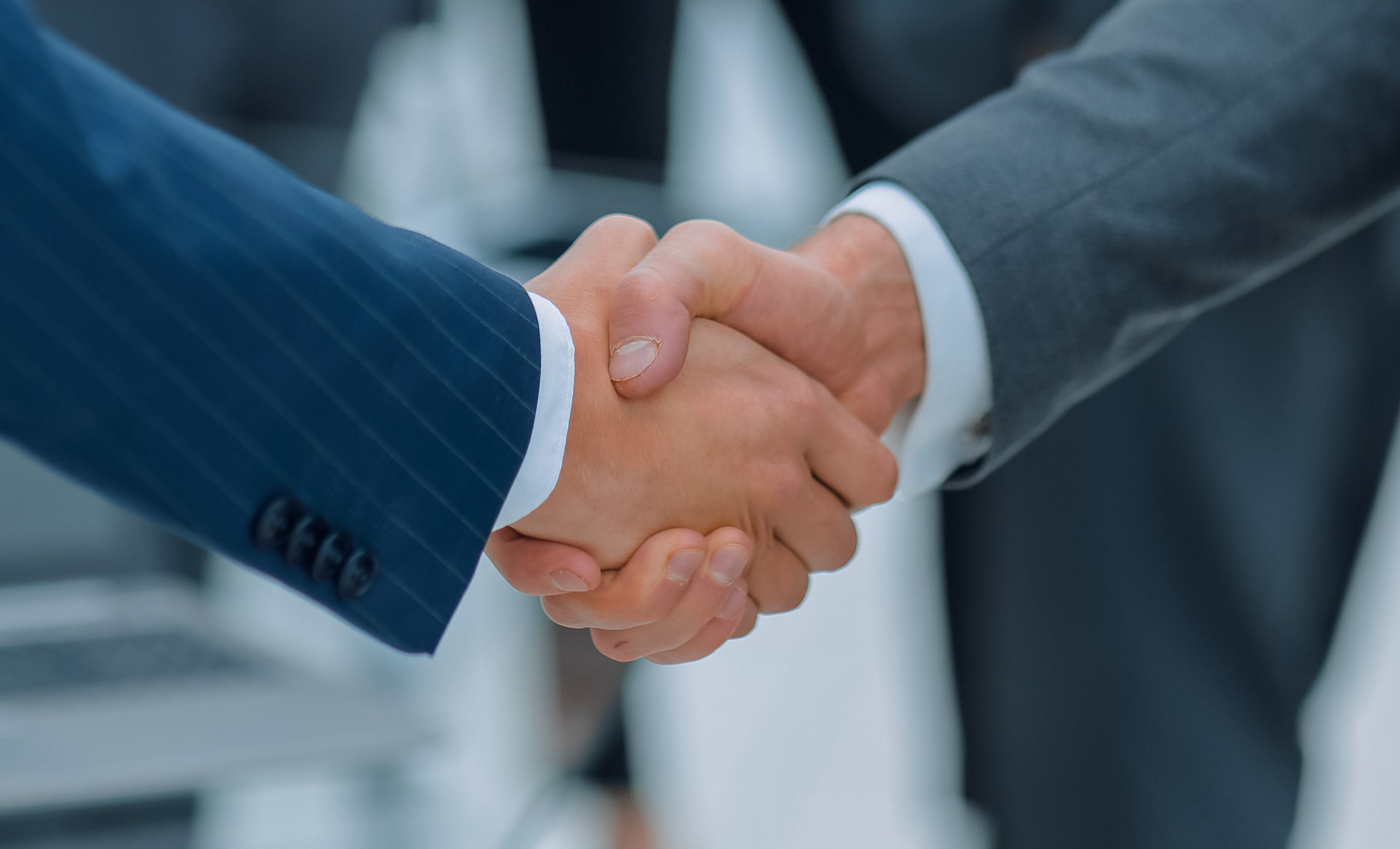 Two,Businessmen,Shaking,Hands,With,Colleagues,On,Background.